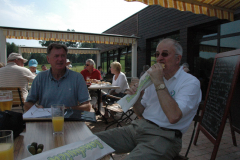 Rick Jones looks on as Mike Houghton enjoys a French delicacy.